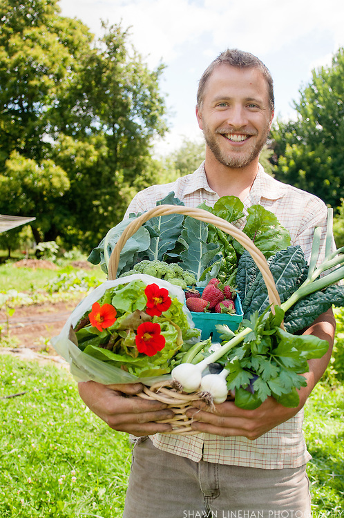 Conner Voss holds a CSA basket from his Diggin Roots Farm.