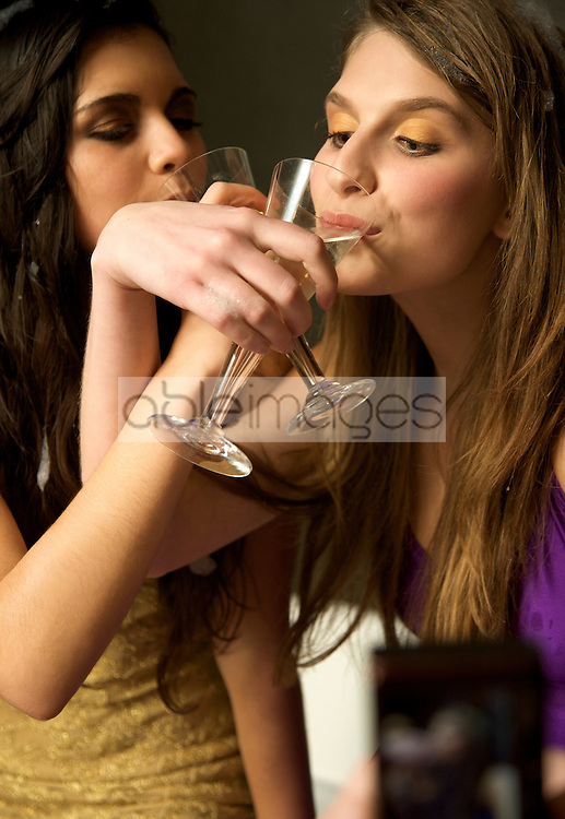 Close up of two girls drinking champagne with crossed arms