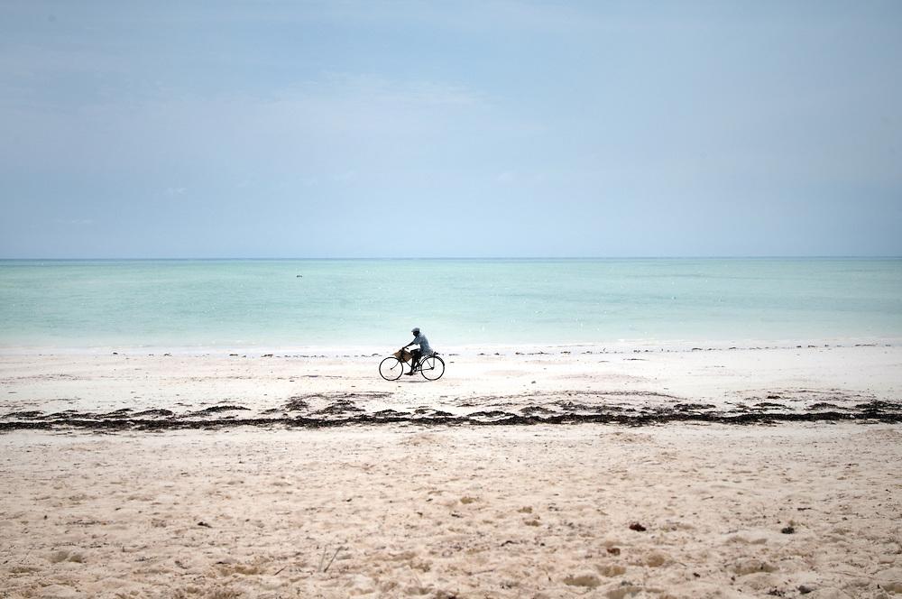 Zanzibar, Tanzania. A man bikes across the beach.