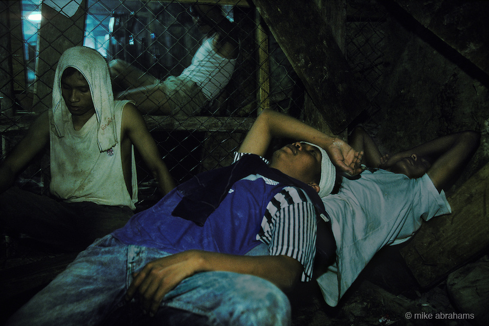 Exhausted miners resting in the dangerous and cramped tunnels with no regard for health and safety in the rush for gold. Mount Diwata, Mindanao, The Philippines.