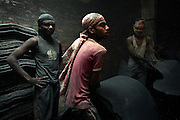 Three young men are working in a dark, dusty room where they smooth and cut leather in Jajmau Industrial Area, Kanpur, Uttar Pradesh. Labourers use almost no protection against the cancerogenic particles generated by this industrial process.