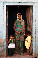 Shanno, 24, is 9 months pregnant with her 4th child as she stands with 2 of her 3 children at the door of her rented house in a slum in Tonk, Rajasthan, India, on 20th June 2012. Shanno was married at the age of 17 and had successive children which affected her health and her children's health because she was unable to breastfeed them and was too poor to raise them properly. She had also given one of her sons to her sister at birth. Photo by Suzanne Lee for Save The Children UK