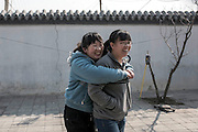 Pan Xin, left, diagnosed with Autism plays with one of the educators inside Vila Rosa Residential Open Unit for people with mental health conditions in Yinqing district, Beijing, China. Photo by Xaume Olleros