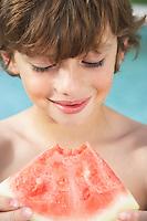 Boy (7-9) eating watermelon close-up