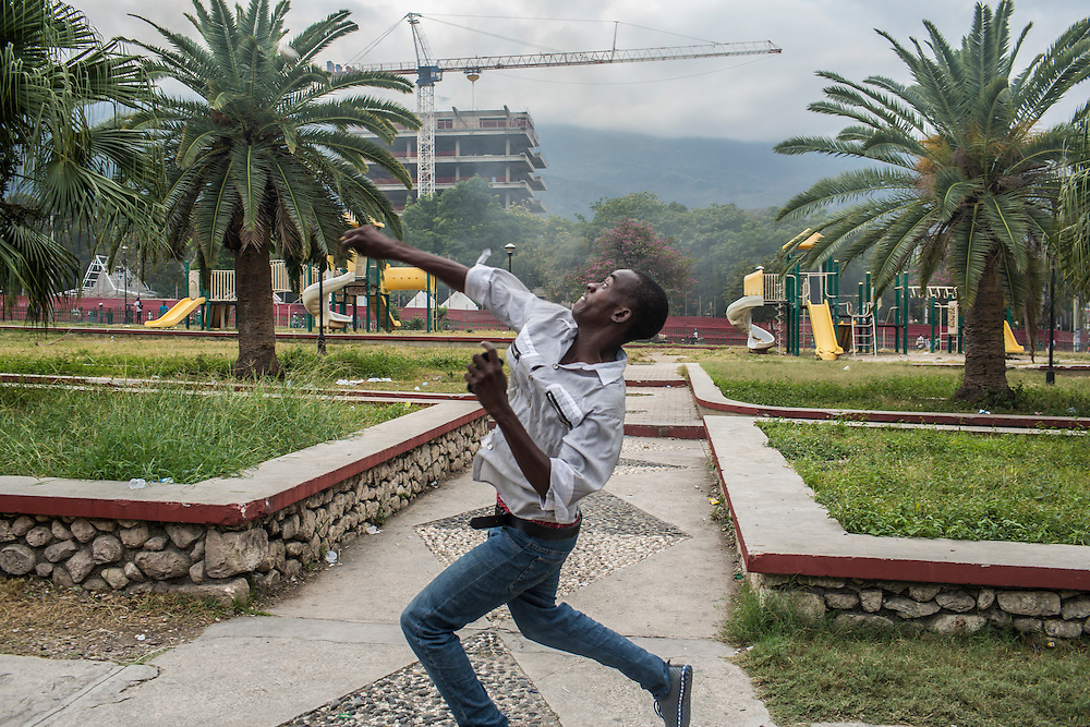 An anti-government protester throws a rock at pro-government supporters on Tuesday, December 16, 2014 in Port-au-Prince, Haiti. President Michel Martelly was elected in 2010 with great hope for reforms, but in the wake of slow recovery and parliamentary elections that are three years overdue, his popularity has suffered tremendously, forcing Prime Minister Laurent Lamothe to resign.