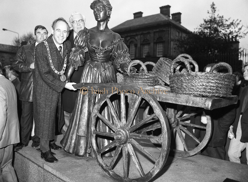 """Molly Malone Statue Unveiled. (R93)..1988..20.12.1988..12.20.1988..20th December 1988..""""Dublin's Fair City"""" received a millenniun gift to commemorate her most famous daughter, Molly Malone, when Jurys Hotel Group plc presented a specially commissioned sculpture to the people of Dublin. The sculpture was formally handed over by Michael McCarthy, MD,Jurys Hotel Group, to the Lord Mayor of Dublin, Councillor Ben Briscoe, TD, in an unveiling ceremony today at the corner of Grafton Street, Suffolk Street and Nassau Street..Molly Malone was created and fashioned in her traditional 17th century dress by Dublin born artist, Jeanne Rynhart, who was selected from a number of entries for the statue design, by the Dublin Millennium Board...Image shows Councillor Ivor Callely ,Lord Mayor, Ben Briscoe and City Manager, Frank Feely 'helping' Molly with her cart."""