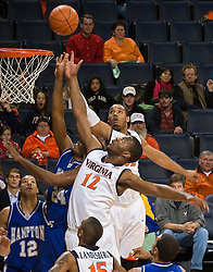 Virginia forward Jamil Tucker (12) and forward Mike Scott (32) battle Hampton's George DeGroat (24) for a rebound.  The Virginia Cavaliers defeated the Hampton Pirates 74-48 at the John Paul Jones Arena on the Grounds of the University of Virginia in Charlottesville, VA on December 23, 2008. (Special to the Daily Progress / Jason O. Watson)
