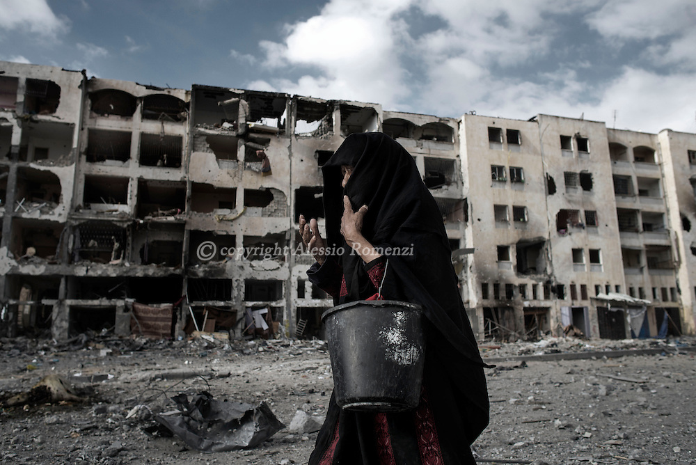 Gaza Strip, Beit Lahia: A Palestinian woman is seen as she walks in front of destroyed buildings in Beit Lahia, located less than two kilometres from the northern crossing point between Israel and the Gaza Strip on August 2, 2014. ALESSIO ROMENZI