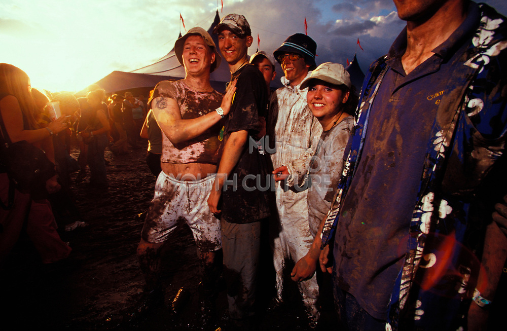 A group of muddy people with hats, Glastonbury, U.K, 2000s.