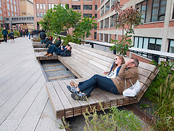 People relaxing on wooden benches at the new High Line elevated landscaped public walkway built on old railway viaduct in Chelsea district of Manhattan in New York City USA