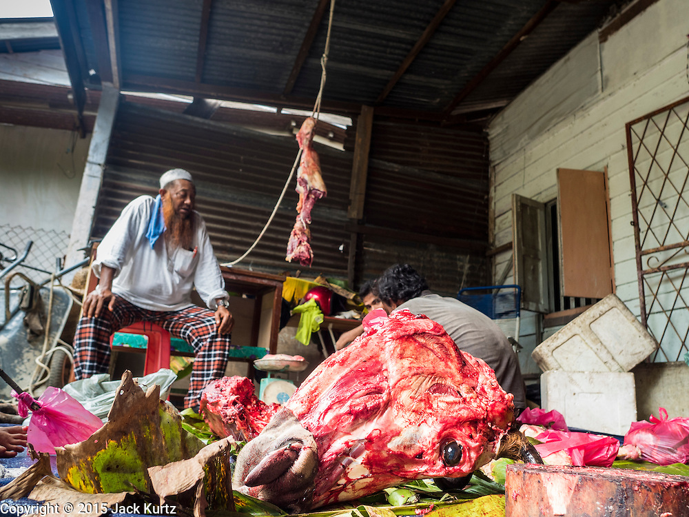 01 JUNE 2015 - KULAI, JOHORE, MALAYSIA:  A cow is butchered in an informal meat shop in the Rohingya refugee community in Kulai, Malaysia. The UN says the Rohingya, a Muslim minority in western Myanmar, are the most persecuted ethnic minority in the world. The government of Myanmar insists the Rohingya are illegal immigrants from Bangladesh and has refused to grant them citizenship. Most of the Rohingya in Myanmar have been confined to Internal Displaced Persons camp in Rakhine state, bordering Bangladesh. Thousands of Rohingya have fled Myanmar and settled in Malaysia. Most fled on small fishing trawlers. There are about 1,500 Rohingya in the town of Kulai, in the Malaysian state of Johore. Only about 500 of them have been granted official refugee status by the UN High Commissioner for Refugees. The rest live under the radar, relying on gifts from their community and taking menial jobs to make ends meet. They face harassment from Malaysian police who, the Rohingya say, extort bribes from them.       PHOTO BY JACK KURTZ