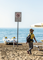THEMENBILD - ein Schild am Strand, mit dem Hinweis, dass man sich strafbar macht, wenn man Dienste von Masseuren in Anspruch nimmt oder Produkte von Strandverkäufern kauft. Eine Masseurin geht auf dem Strand. Lignano ist ein beliebter Badeort an der italienischen Adria-Küste, aufgenommen am 16. Juni 2019, Lignano Sabbiadoro, Italien //  a sign on the beach indicating that you are liable to prosecution if you use the services of masseurs or buy products from beach vendors. A masseuse walks on the beach. Lignano is a popular seaside resort on the Italian Adriatic coast on 2019/06/16, Lignano Sabbiadoro, Italy. EXPA Pictures © 2019, PhotoCredit: EXPA/ Stefanie Oberhauser
