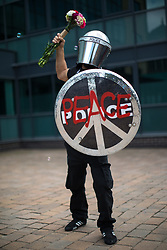 © Licensed to London News Pictures . 26/08/2017. Manchester , UK. A man wearing a costume in homage to a Banksy stencil , featuring use of decommissioned police riot shield and helmet . 2017 Pride parade through Manchester City Centre . The annual festival , which is the largest of its type in Europe , celebrates LGBT life . Photo credit : Joel Goodman/LNP