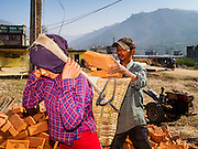 02 MARCH 2017 - SANKHU, NEPAL: Laborers load bricks into a basket before carrying them to a home being rebuilt in Sankhu. Each basket weighs about 80 pounds. Almost all of the work is being done by hand. There is more construction and rebuilding going on in Sankhu, west of central Kathmandu, than in many other parts of the Kathmandu Valley nearly two years after the earthquake of 25 April 2015 that devastated Nepal. In some villages in the Kathmandu valley workers are working by hand to remove ruble and dig out destroyed buildings. About 9,000 people were killed and another 22,000 injured by the earthquake. The epicenter of the earthquake was east of the Gorka district.   PHOTO BY JACK KURTZ