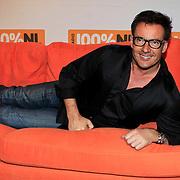 NLD/Hilversum/20130109 - Uitreiking 100% NL Awards 2012, Gerard Joling liggend op een oranje bank