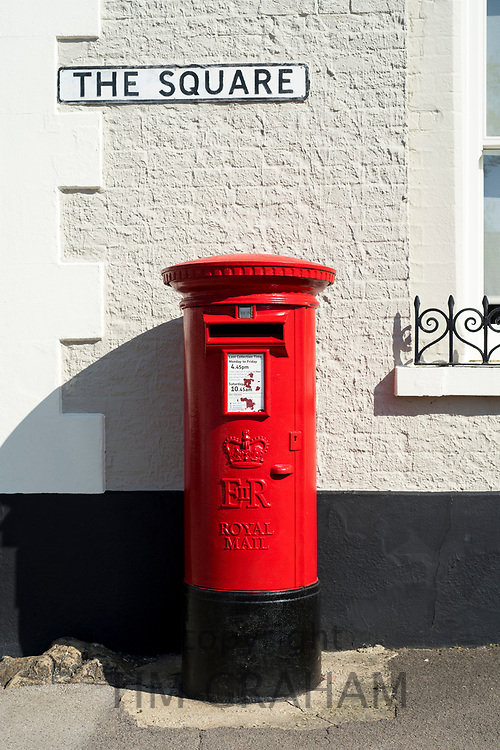 Traditional bright red painted EIIR pillar box mailbox - ER postbox - of Royal Mail and sign for The Square in Ramsbury, Wiltshire
