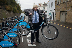 © Licensed to London News Pictures.13/12/2013. London, UK. Mayor of London, Boris Johnson lift a bicycle up during the launch of the south west expansion of the Barclays Cycle Hire into Hammersmith & Fulham and Wandsworth.Photo credit : Peter Kollanyi/LNP