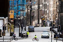 Edinburgh, Scotland, UK. 18 April 2020. Views of empty streets and members of the public outside on another Saturday during the coronavirus lockdown in Edinburgh. A family cycles past the empty Royal Mile. Iain Masterton/Alamy Live News