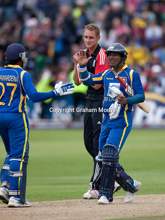 England captain Stuart Broad watches as Sri Lankan batsmen Mahela Jayawardene and Kumar Sangakkara (right) celebrate winning the T20 international at Bristol.  Photo: Graham Morris/photosport.co.nz