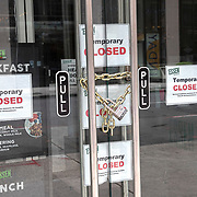 Chains are seen on a restaurant door as Manhattan remains virtually empty with closed businesses and limited traffic due to the Coronavirus (Covid-19) outbreak in New York City on Monday, May 11, 2020.  Nonessential businesses have been closed and large gatherings have been banned across the state since March 22 under an emergency order issued by Governor Cuomo that is set to expire on Friday. (Alex Menendez via AP)