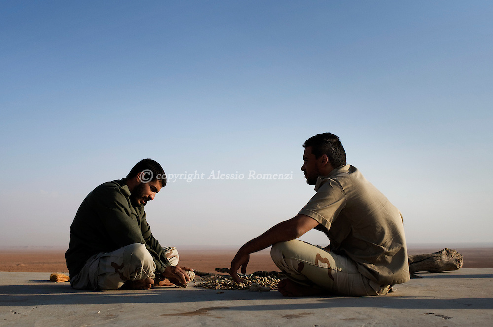 LIBYAN ARAB JAMAHIRIYA, Twama : Libyan rebels crack almonds in the outpost of Twama, 30 km south-east of the western stronghold Zintan, on July 15, 2011. The lone outpost is the last defensive position of the rebels in the south of the Nafusa mountains.ALESSIO ROMENZI