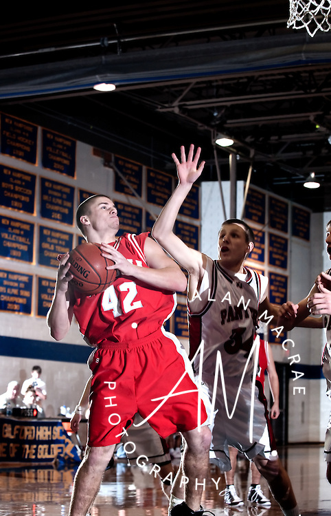 Laconia's Brian Bozek tries to get a shot off under pressure from MA's Patrick Cotter in Tuesday's championship game in the 35th Annual Holiday Tournament at Gilford High School.  (Alan MacRae/for the Laconia Daily Sun)