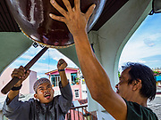 25 JUNE 2017 - BANGKOK, THAILAND: Men bang a community drum at Bang Luang Mosque in Bangkok to announce the end of Ramadan after Eid al-Fitr prayers in the mosque. Eid al-Fitr is also called Feast of Breaking the Fast, the Sugar Feast, Bayram (Bajram), the Sweet Festival or Hari Raya Puasa and the Lesser Eid. It is an important Muslim religious holiday that marks the end of Ramadan, the Islamic holy month of fasting. Muslims are not allowed to fast on Eid. The holiday celebrates the conclusion of the 29 or 30 days of dawn-to-sunset fasting Muslims do during the month of Ramadan. Islam is the second largest religion in Thailand. Government sources say about 5% of Thais are Muslim, many in the Muslim community say the number is closer to 10%.    PHOTO BY JACK KURTZ