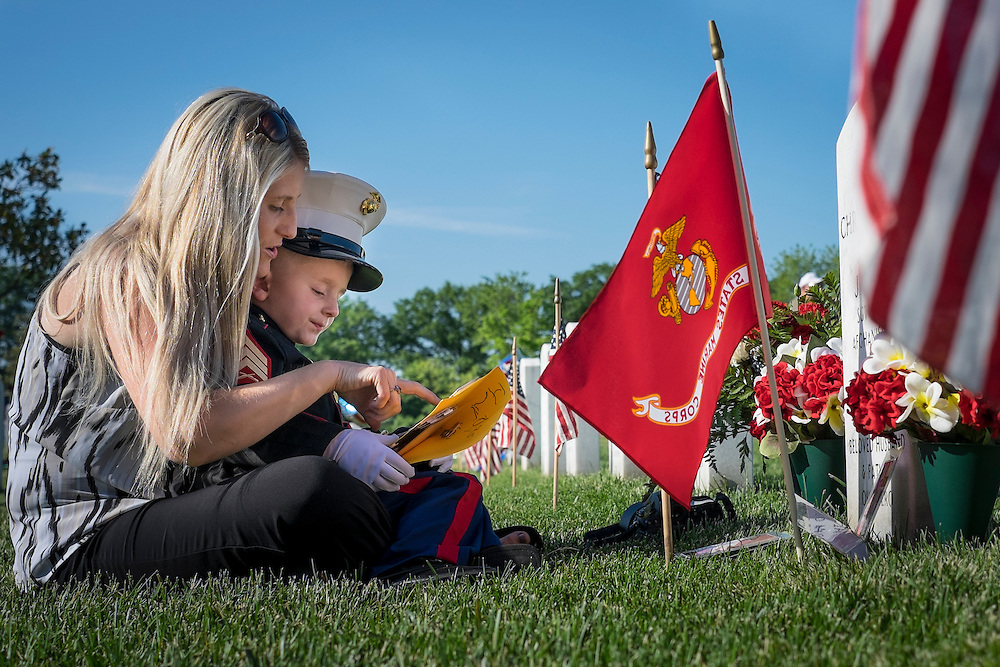 On Memorial Day, Brittany Jacobs of Hertford, North Carolina and her son, Christian, 4 sit at the headstone of her husband, Marine Sgt. Christopher Jacobs, in Section 60 at Arlington National Cemetery in Arlington, Virginia, USA, on 25 May 2015.
