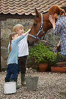 Mother and children (5-6 7-9) stroking horse outside stable