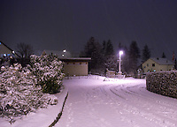 A snowy street scene at night in Zufikon, Switzerland.