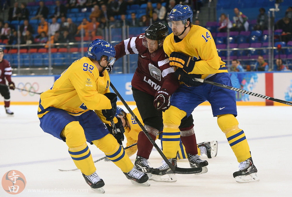 Feb 15, 2014; Sochi, RUSSIA; Latvia forward Janis Sprukts (5) is checked by Sweden forward Patrick Berglund (14) as Sweden forward Gabriel Landeskog (92) attempts to get the puck in a men's preliminary round ice hockey game during the Sochi 2014 Olympic Winter Games at Shayba Arena.