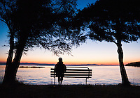 A woman sitting on a bench at County Park, San Juan Island watching the sun set over Haro Strait and the Gulf Islands of British Columbia.  Washington, USA.