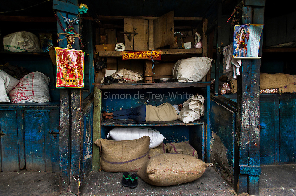 19th February 2014,New Delhi. A man sleeps on shelving in a market in Old Delhi, India on the 19th February 2014<br /> <br /> Sleeping in the outdoors is common in Asia due to a warmer climate and the fact that personal privacy for sleep is not so culturally ingrained as it is in the West. New Delhi (where most of these images were taken) is a harsh city both in climate and environment and for those working long hours, often in hard manual labour, sleep and rest is something fallen into when exhaustion overwhelms, no matter the place or circumstance. Then there are the homeless, in Delhi figures for them from Government and NGO sources vary wildly from 25,000 to more than 10 times that. Others public sleepers may simply be travellers having a siesta along the way.<br />  <br /> <br /> PHOTOGRAPH BY AND COPYRIGHT OF SIMON DE TREY-WHITE, photographer in Delhi<br /> <br /> + 91 98103 99809<br /> email: simon@simondetreywhite.com