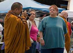 A monk in a yellow robe takes photos at a Farmer's Market with two adult women watching, Mendocino, California, USA.