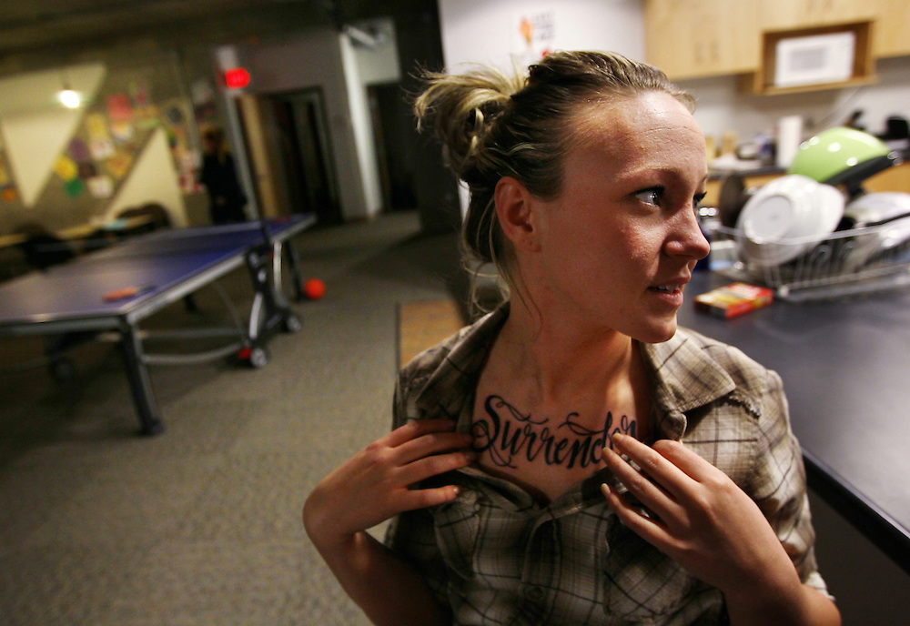 """3/7/11 6:36:41 PM -- Minneapolis, MN, U.S.A.---.Kayla Forsythe, 21, of Mankato, MN, shows friends the tattoo she got earlier in the day while sitting in the common area of the women's flat in StepUP housing at Augsburg College in downtown Minneapolis March 7, 2011.  According to Forsythe, the word """"Surrender"""" on her chest reminds her that her way isn't the best way.  .---.Photo by Courtney Perry, Freelance."""