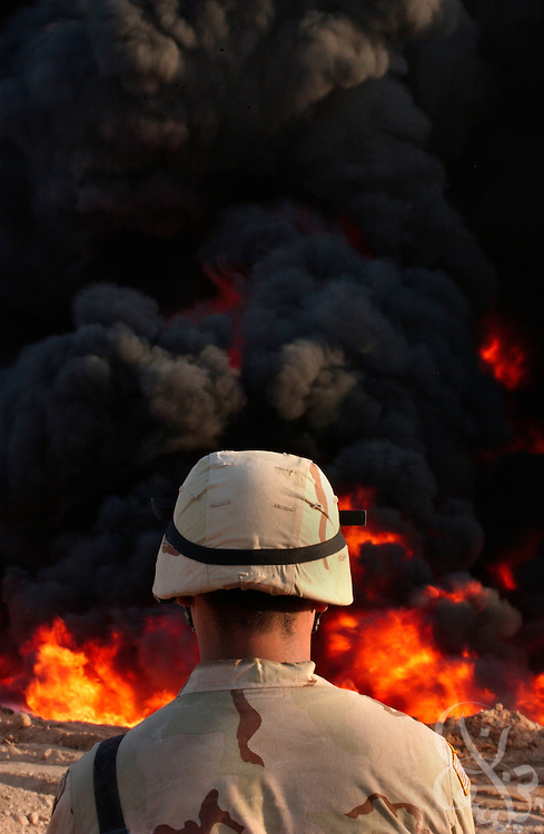 A U.S. 101st Airborne soldier watches as a section of ruptured Iraqi oil pipeline burns in the Northern Iraqi town of Ash Sharqat August 18, 2003.  The thousand kilometer Iraqi pipeline, which carries valueable oil exports northward to Turkey, often is the target of attacks.
