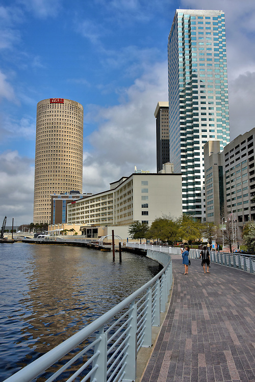 Tampa Riverwalk Near Downtown Tampa, Florida<br /> The Hillsborough River flows for almost 60 miles before emptying into Tampa Bay. The best way to see some of its prettiest scenery is to stroll along the Tampa Riverwalk. This pedestrian walkway will take you along downtown, through parts of the arts district and next to several parks. You will also see several statues and busts of local historic figures. Eventually this beautiful trail will extend about 2.5 miles. The two towers in the background are the Bank of America and Rivergate.  The latter is commonly called the Beercan building.