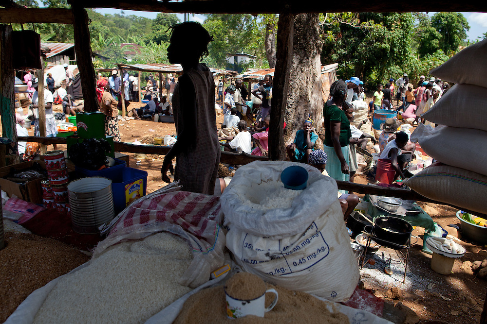 An open air market. The Inter-American Development Bank is funding this road project in the south of Haiti, aiming to cut travel time and transportation costs, and to improve living conditions in the southern provinces. This 50-mile stretch of road connects the small cities of Les Cayes and Jeremie and many rural villages in between. A Brazilian company, OAS, is doing the construction. The road is far from complete, but is already transforming commerce and daily life in the area. Travel time has been cut in half; fewer trucks are breaking down, so less food is spoiled; and farmers are planting more crops in anticipation of more dependable farm-to-market transportation.