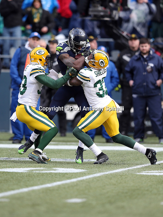 Seattle Seahawks wide receiver Ricardo Lockette (83) shoves his forearm into the face of Green Bay Packers free safety Ha Ha Clinton-Dix (21) as he gets gang tackled by Clinton-Dix and Green Bay Packers free safety Micah Hyde (33) as he catches a second quarter pass for a first down at the Packers 41 yard line during the NFL week 20 NFC Championship football game against the Green Bay Packers on Sunday, Jan. 18, 2015 in Seattle. The Seahawks won the game 28-22 in overtime. ©Paul Anthony Spinelli
