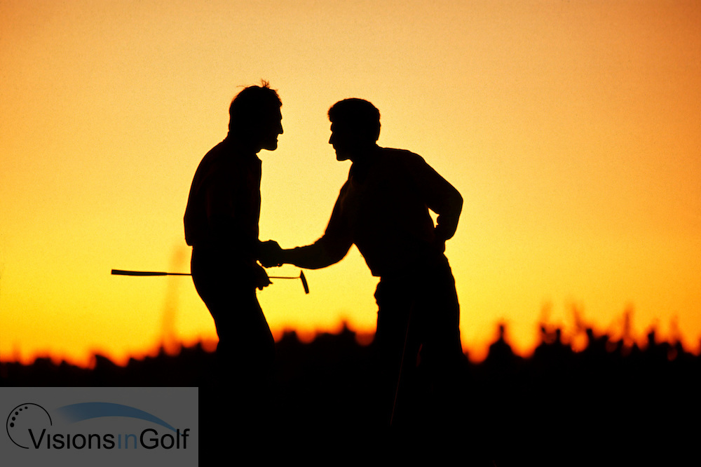 910921\KIAWAH ISLAND, SOUTH CAROLINA<br /> USA/PHOTO MARK NEWCOMBE/29th RYDER CUP<br /> <br /> SEVE BALLESTEROS AND JOSE MARIA OLAZABAL AT THE END OF THE SECOND DAY<br /> SEVE &amp; OLAZABAL CONGRATULATE EACH OTHER AFTER GAINING A HALF ON SATURDAY EVENING ON THE 18TH GREEN AS THE SUN SETS.<br /> 29th RYDER CUP <br /> SEPTEMBER 1991<br /> KIAWA ISLAND, SOUTH CAROLINA<br /> USA