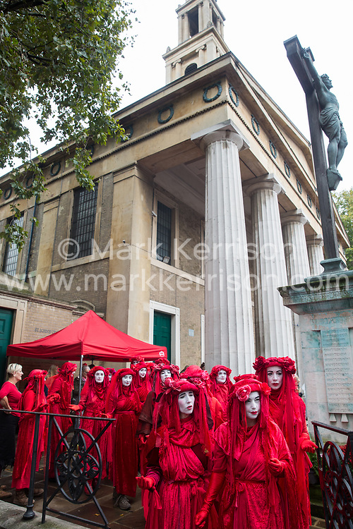 London, UK. 16 October, 2019. Extinction Rebellion's Red Brigade leave St John's church at Waterloo to take part in the day's International Rebellion Autumn Uprising protests outside Google and YouTube against the spread of systematic disinformation on climate change and in Trafalgar Square and Whitehall against the use by the Metropolitan Police of Section 14 so as to prohibit entirely Extinction Rebellion Autumn Uprising protests throughout the capital. Credit: Mark Kerrison/Alamy Live News