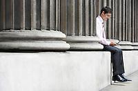 Businessman sitting between pillars outside building sending text message
