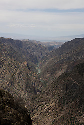 View of the Black Canyon and the Gunnison River from the South Rim Road.  Black Canyon of the Gunnison National Park is a United States National Park located near Montrose, Colorado in the western part of the state. The park is managed by the National Park Service. There are two entrances to the park; the more-developed south rim entrance is located 15 miles (24 km) east of Montrose, while the north rim entrance is located 11 miles (18 km) south of Crawford and is closed in the winter. The park contains 12 miles of the 48 mile long canyon of the Gunnison river. The park contains the deepest and most dramatic section of the canyon, one of the deepest mountain descents in North America.  The canyon continues upstream into the Curecanti National Recreation Area and downstream into the Gunnison Gorge National Conservation Area.