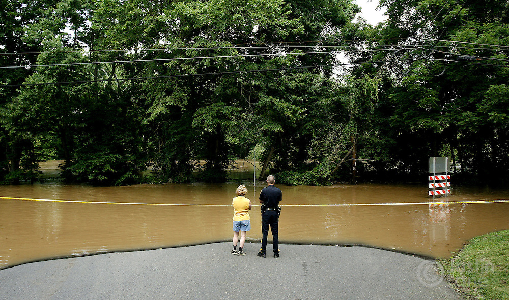 A police officer and a resident look over the flood waters of the Delaware River on River Road in Lower Mayfield Township, Pennsylvania on Thursday 29 June 2006. Heavy rains earlier in the week swelled rivers across the Northeastern United States, killing at least 11 people and forcing hundreds of thousands to evacuate their homes.