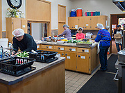 """26 FEBRUARY 2020 - FARMINGTON, MINNESOTA: Volunteers at the community dinner at Faith Church, work in the kitchen before the dinner. Faith Church is a United Methodist Church in Farmington, MN, about 30 minutes south of the Twin Cities. The dinner is sponsored by Loaves & Fishes, a Christian organization that provides food for community dinners and foodbanks. Farmington, with a population of 21,000, is a farming community that has become a Twin Cities suburb. The city lost its only grocery store, a Family Fresh Market, in December, 2019. The closing turned the town into a """"food desert."""" In January, Faith Church started serving the weekly meals as a response to the store's closing. About 125 people per week attend the meal at the church, which is just a few blocks from the closed grocery store. The USDA defines food deserts as having at least 33% or 500 people of a census tract's population in an urban area living 1 mile from a large grocery store or supermarket. Grocery chains Hy-Vee and Aldi both own land in Farmington but they have not said when they plan to build or open stores in the town.     PHOTO BY JACK KURTZ"""