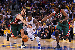 Mar 16, 2012; Oakland, CA, USA; Golden State Warriors point guard Nate Robinson (2) dribbles past Milwaukee Bucks small forward Carlos Delfino (left) and forward Ekpe Udoh (right) during the fourth quarter at Oracle Arena. Milwaukee defeated Golden State 120-98. Mandatory Credit: Jason O. Watson-US PRESSWIRE