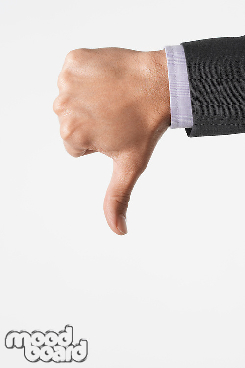 Man making thumbs-down sign against white background close-up of hand