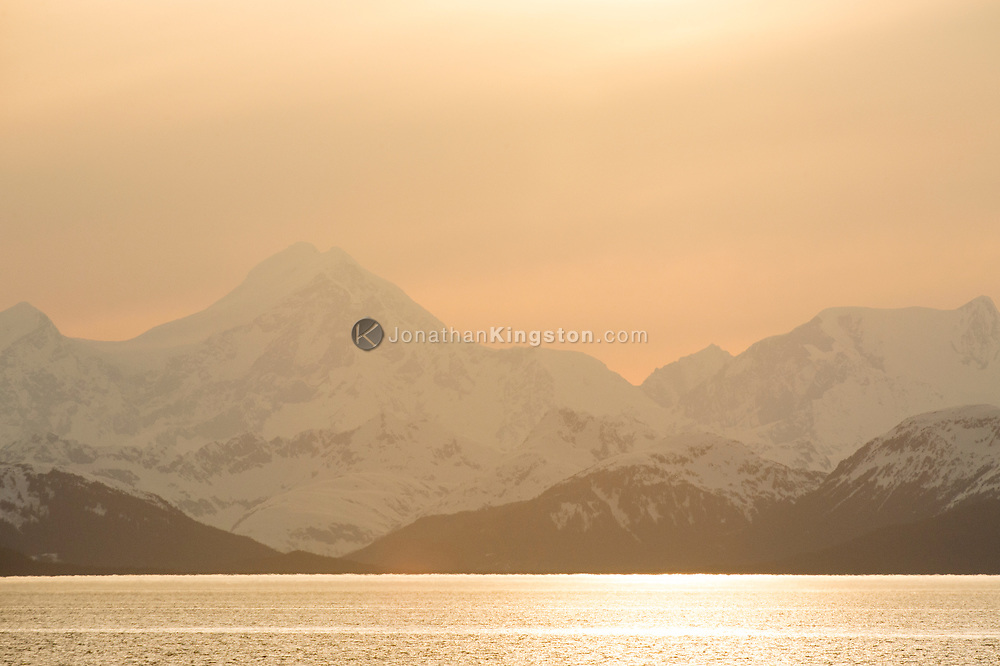 Sunset over snow capped peaks of Glacier Bay National Park.