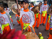 "05 JULY 2014 - BANGKOK, THAILAND:  A drummer performs for Chinese style lion dancers in Bangkok during a parade for vassa. Vassa, called ""phansa"" in Thai, marks the beginning of the three months long Buddhist rains retreat when monks and novices stay in the temple for periods of intense meditation. Vassa officially starts July 11 but temples across Bangkok are holding events to mark the holiday all week.   PHOTO BY JACK KURTZ"