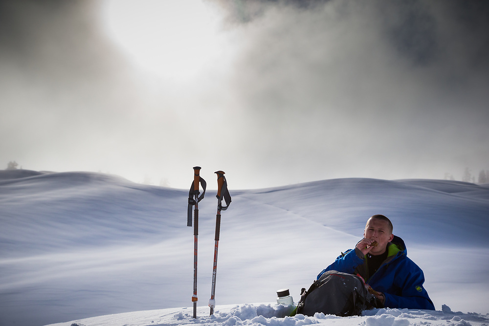 Tyler Hatcher takes a break from skinning up and eats some food in the Cascade backcountry as a winter storm clears.